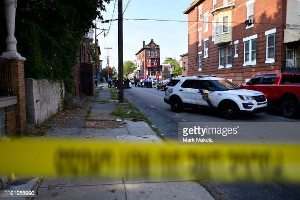 Police officers congregate while responding to a shooting on August 14, 2019 in Philadelphia, Pennsylvania. At least six police officers were...