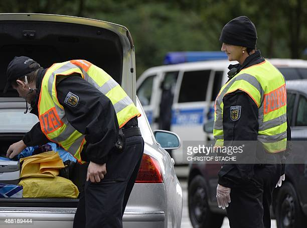 Police officers control a car at a parking spot at the GermanAustria border near the village of Passau southern Germany on September 14 2015 Honking...