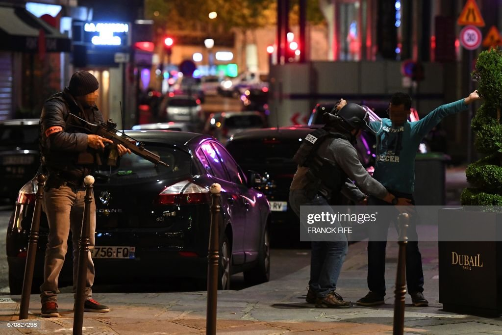 Police officers control a man on the Champs Elysees in Paris after a shooting on April 20, 2017. One police officer was killed and another wounded today in a shooting on Paris's Champs Elysees, police said just days ahead of France's presidential election. France's interior ministry said the attacker was killed in the incident on the world famous boulevard that is popular with tourists. FIFE