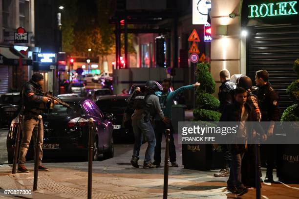 Police officers control a man on the Champs Elysees in Paris after a shooting on April 20 2017 One police officer was killed and another wounded...