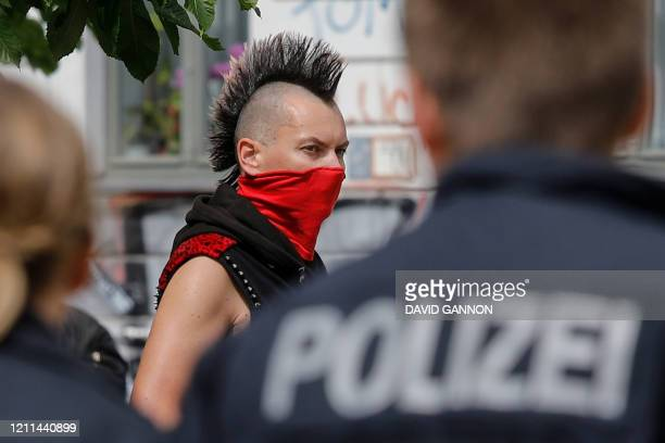 Police officers control a small group of protesters including a punk in Berlin's Kreuzberg district on May 1 during a May Day protest amid the...