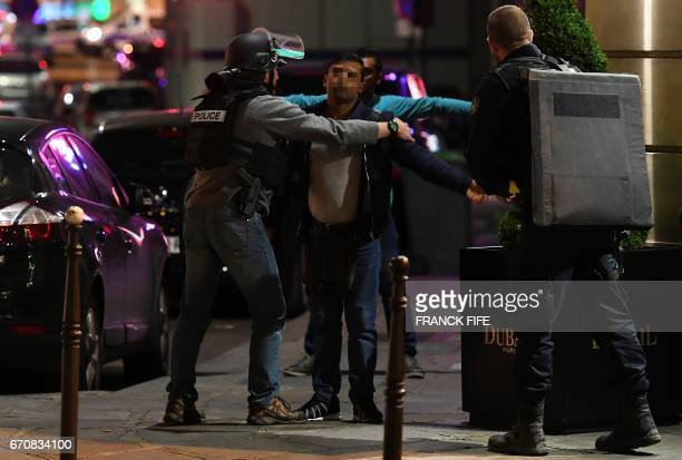 Police officers control men near the site of a shooting at the Champs Elysees in Paris on April 20 2017 French antiterror prosecutors said they...