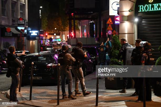 Police officers control passersby near the Champs Elysees in Paris after a shooting on April 20 2017 One police officer was killed and another...