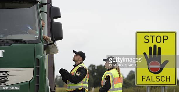 Police officers control the ID of a truck driver coming from Austria by a giant sign reading 'Stop wrong' at a highway slip road at the...