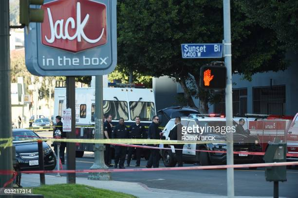 Police officers converse outside a Jack in the Box restaurant in Hollywood California January 31 after police shot and killed a knifewielding suspect...