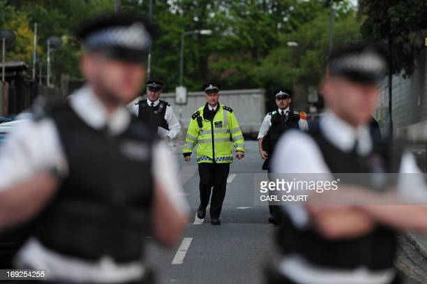 Police officers cordon off a road area in Woolwich east London on May 22 following an incident in which one man was killed and two others seruiously...
