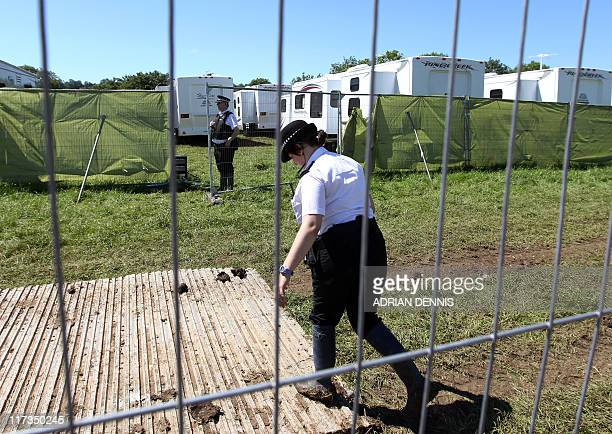 Police officers cordon off a VIP area after a body of a man was discovered in a toilet during the last day of the Glastonbury festival near...