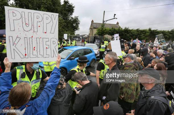 Police officers cordon off the factory entrance as workers leave during the demonstration. Protesters from all over the country joined Camp Beagle to...