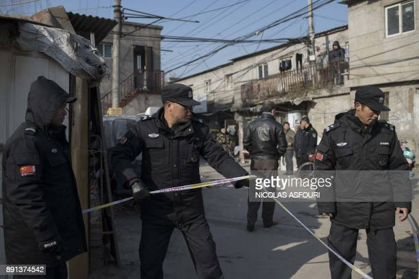 Police officers cordon off the site of a fire in a low income neighbourhood in Beijing on December 13 2017 A building fire killed five people and...