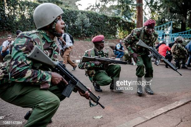 Police officers cover themselves from gunshots at the scene of an explosion at a hotel complex in Nairobi's Westlands suburb on January 15 in Kenya A...