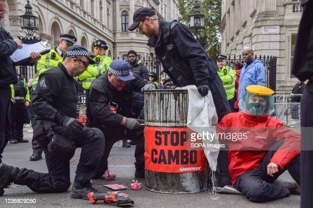 Police officers cut through a barrel to remove an activist during the Stop Cambo protest. Greenpeace activists locked themselves to barrels and...