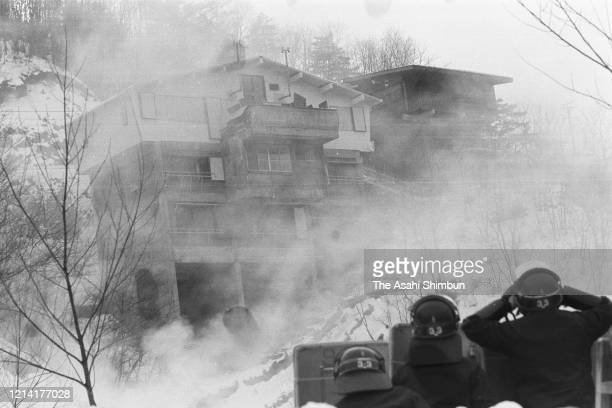 Police officers defending themselves with shields look the Asama Sanso lodge as the United Red Army members take a hostage on February 22 1972 in...