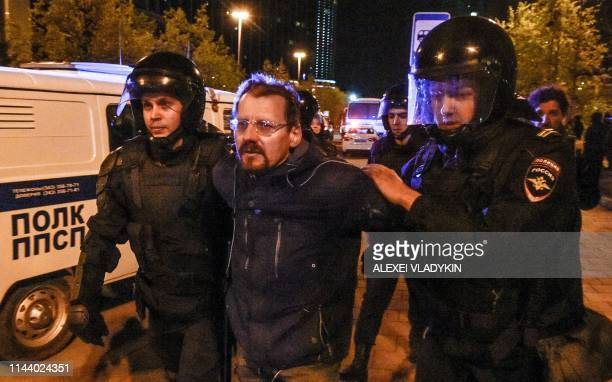 Police officers detain a activist protesting against a plan to build an Orthodox cathedral at a construction site in a park in the Russian Urals city...