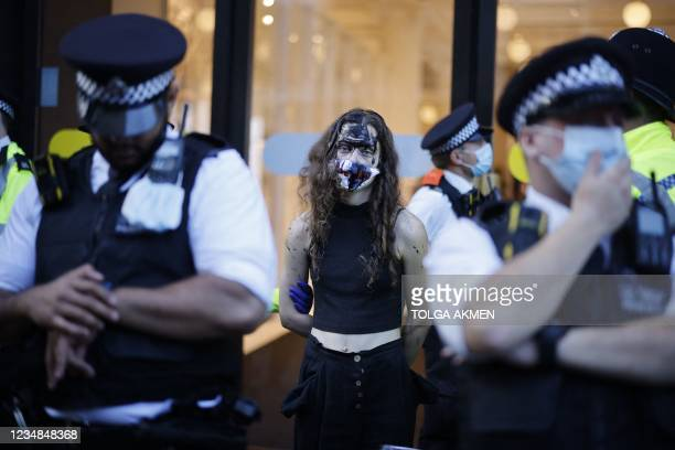 Police officers detain a climate activist from the Extinction Rebellion group outside the Selfridges store in central London on August 24, 2021 where...