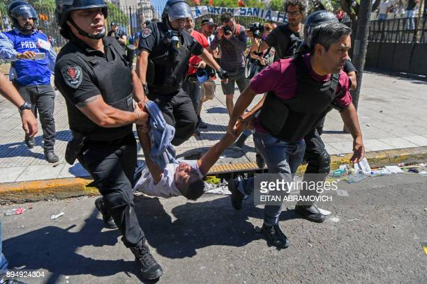 Police officers detain a demonstrator during clashes in a protest against the proposed pension reforms outside the Congress in Buenos Aires on...