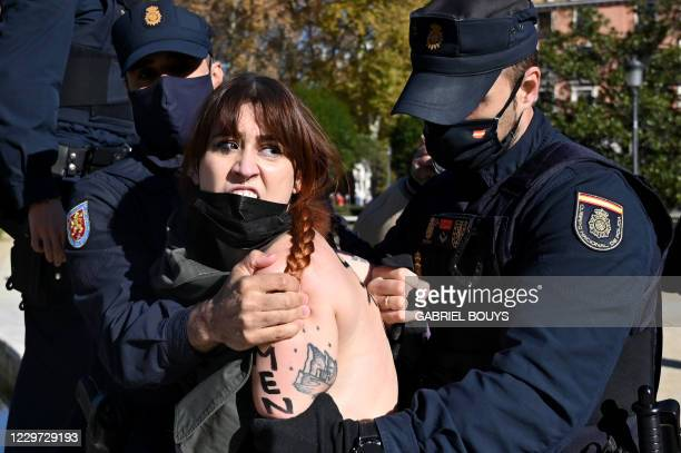 Police officers detain a Femen activist protesting against a demonstration of supporters of former Spanish dictator Francisco Franco, during an...