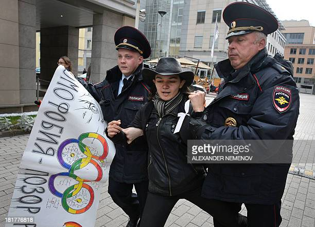 Police officers detain a gay rights activist during an unauthorized protest against hotly disputed Russian laws banning the promotion or display of...