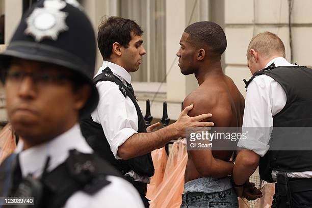 Police officers detain a man near to where a man was stabbed at the Notting Hill Carnival on August 29 2011 in London England The annual carnival...