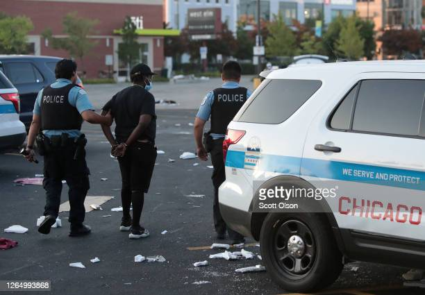 Police officers detain a man who was found inside of a Best Buy store after parts of the city had widespread looting and vandalism, on August 10,...