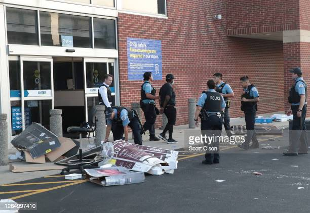 Police officers detain a man who was found inside of a Best Buy store after parts of the city had widespread looting and vandalism on August 10 2020...