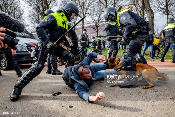 Police officers detain a protester during a protest on the Malieveld against the coronavirus policies and the government on March 14, 2021 in The...