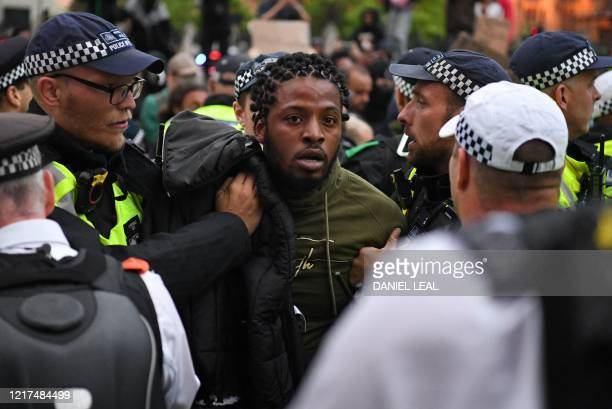 Police officers detain a protestor during an anti-racism demonstration in London, on June 3 after George Floyd, an unarmed black man died after a...