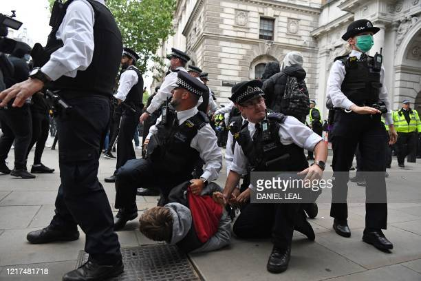 Police officers detain a protestor near the Foreign Office, during an anti-racism demonstration in London, on June 3 after George Floyd, an unarmed...