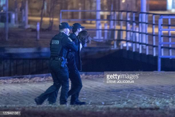 Police officers detain a suspect near the National Assembly of Quebec, in Quebec City, early on November 1 after two people were killed and five...