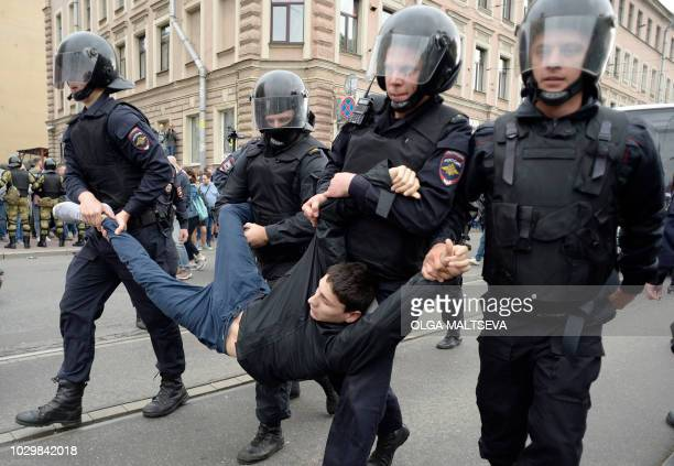 TOPSHOT Police officers detain a young man during a protest rally against planned increases to the nationwide pension age in Saint Petersburg on...