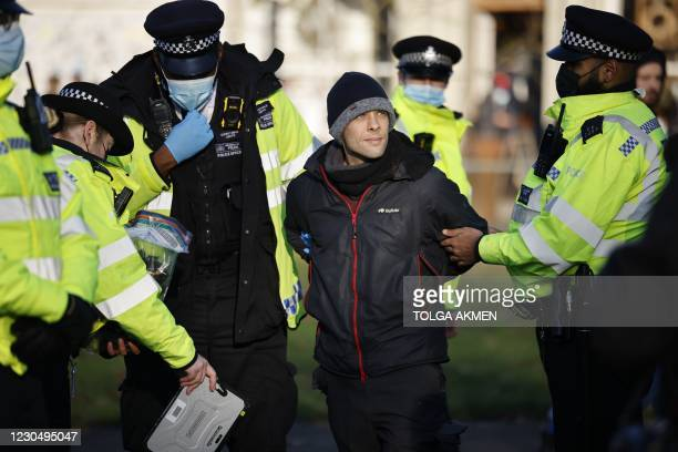 Police officers detain an anti-lockdown protester on Clapham Common, south London, on January 9, 2021 as life continues in Britain's third lockdown...