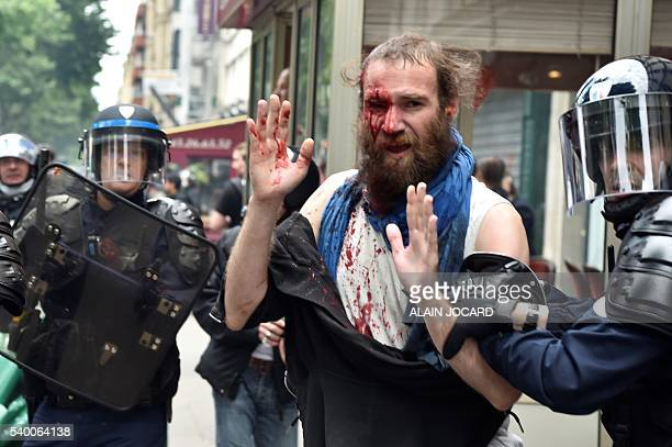 Police officers detain an injured demonstrator during a protest against the French government's planned labour law reforms on June 14 2016 in Paris...