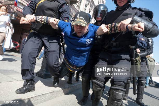 Police officers detain an opposition protester during a May Day rally in Saint Petersburg on May 1 2019 Police in Saint Petersburg on Wednesday broke...