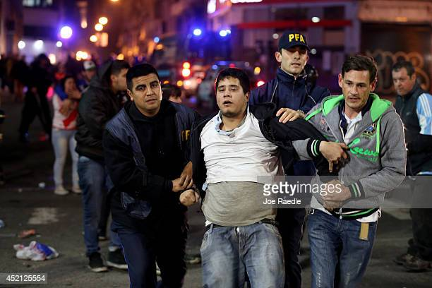 Police officers detain Argentine soccer fans caught after violence erupted near the Obelisco de Buenos Aires after their team lost to Germany 10...