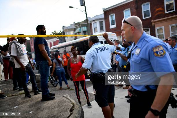 Police officers direct citizens to move back near the scene of a shooting on August 14, 2019 in Philadelphia, Pennsylvania. At least six police...