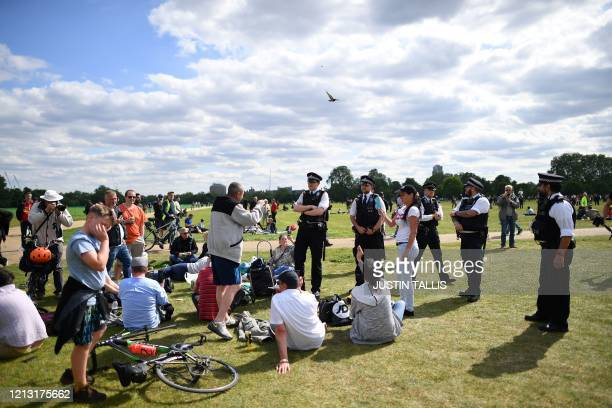 Police officers disperse people who are gathered for an anti-coronavirus lockdown demonstration in Hyde Park in London on May 16 following an easing...