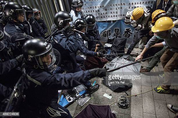 Police officers disperse pro-democracy protesters outside the Legislative Council building after clashes with pro-democracy activists on November 19,...