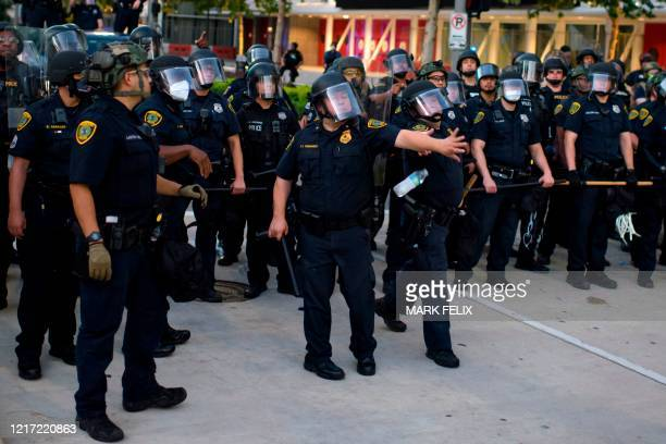 Police officers dodge water bottles after a peaceful march to mourn the death of George Floyd in downtown Houston Texas on Tuesday June 2 2020...