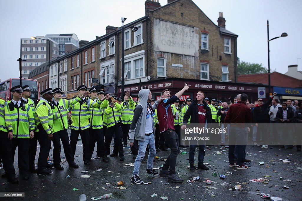 Police officers dodger projectiles as West Ham fans become violent and start throwing bottles at police outside the West Ham United FC's Boleyn Ground on May 10, 2016 in London, England. Tonights Premier League match against Manchester United is West Ham United's last game at the Boleyn Ground, bringing to an end 112 years of the club's history at the ground. The club will move into the Olympic Stadium next season, making way for developers and plans for 800 new homes where the stadium now stands.