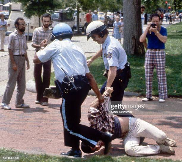 Police officers drag a handcuffed man along a sidewalk in Lafayette Square during a demonstration related to ongoing events in Iran Washington DC mid...
