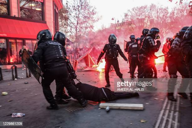 Police officers drag a man on the ground during a protest against the 'global security' draft law, which Article 24 would criminalise the publication...