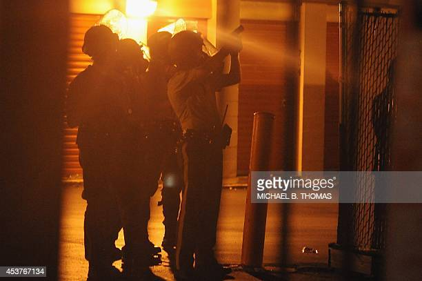 Police officers draw their weapons on a protestor who hid inside a local business on West Florissant Road in Ferguson Missouri on August 17 2014 Riot...