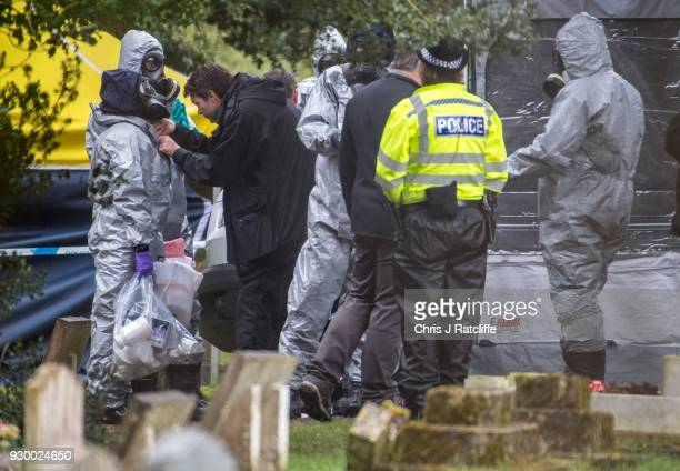 Police officers dress in protective suits and breathing apparatus in London Road cemetery as they continue investigations into the poisoning of...