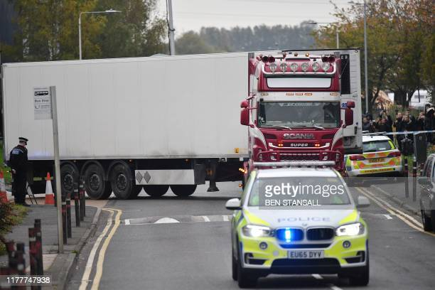 Police officers drive away a lorry in which 39 dead bodies were discovered sparking a murder investigation at Waterglade Industrial Park in Grays,...