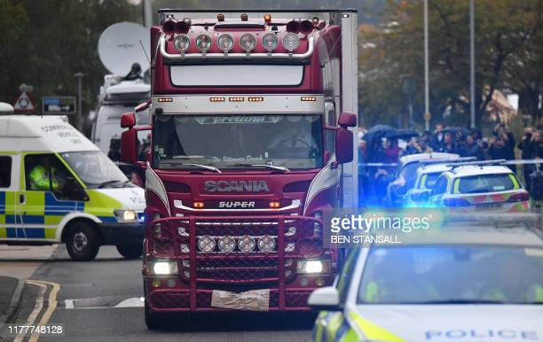Police officers drive away a lorry in which 39 dead bodies were discovered sparking a murder investigation at Waterglade Industrial Park in Grays...