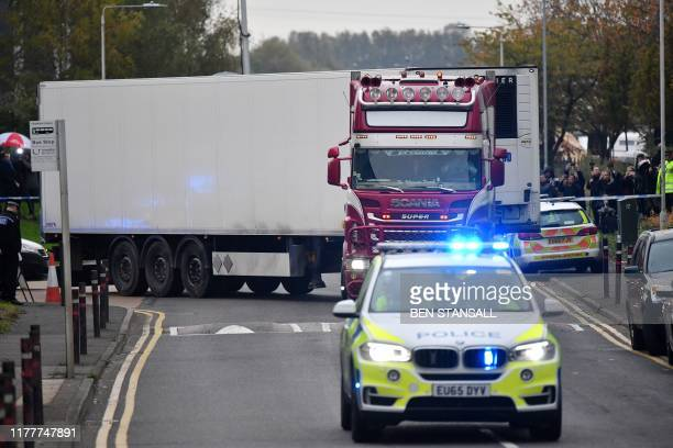 Police officers drive away a lorry in which was discovered 39 dead bodies at Waterglade Industrial Park in Grays east of London on October 23 2019...