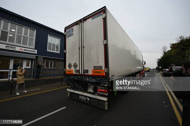 Police officers drive away a lorry with black plastic visible at the rear in which 39 dead bodies were discovered sparking a murder investigation at...