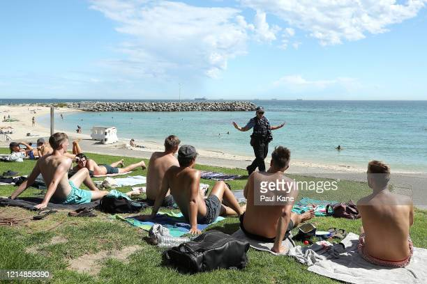 Police officers encourage beach goers to keep 15 metres social distance on March 26 2020 in Perth Australia Further restrictions on travel and...