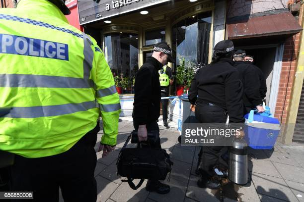 Police officers enter a residential building in Birmingham which was raided by anti-terror forces in the early hours on March 23, 2017. Seven people...