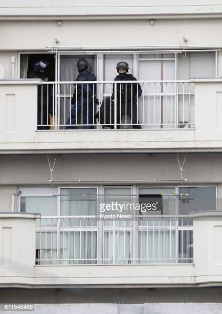 Police officers enter the apartment where a man barricaded himself after shooting his pet dog in Kitakyushu southwestern Japan on Nov 8 2017 Police...