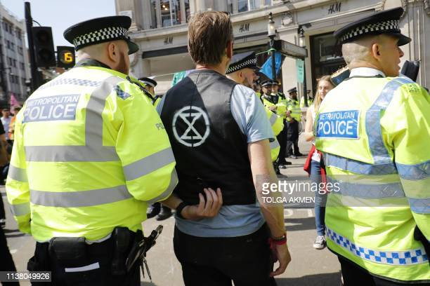 Police officers escort a climate change activist who was occupying the road junction at Oxford Circus in central London on April 19 the fifth day of...